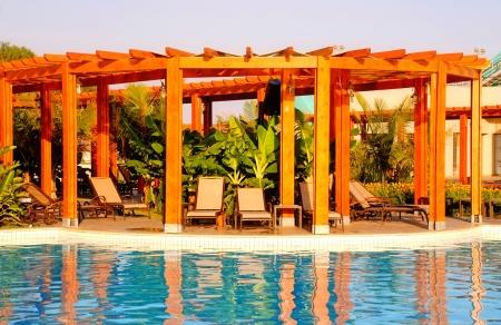 Летний пейзаж с курорта бассейн, деревянные беседки и шезлонги Фото со стока