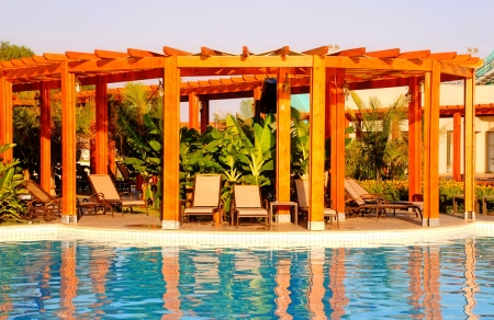 summer landscape with resort swimming pool, wood pergola and deck chairs