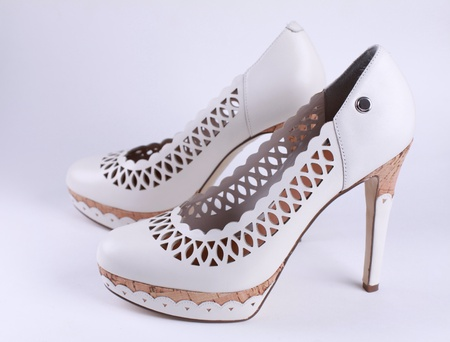 White fashion women's shoes with high heels. Side view photo