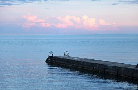 Idyllic seascape with pier, sunset sky and blue sea  photo