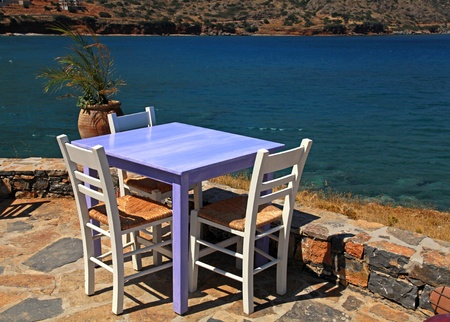 Outdoor restaurant - traditional greek tavern with lilac table and white chairs overlooking Mediterranean sea (Crete, Greece ).  photo
