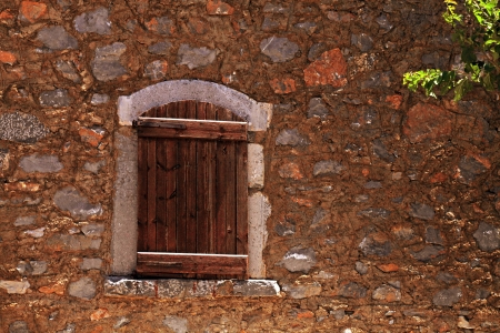 Closed window with rough wooden shutters in old stone wall of ancient rural mediterranean house(Greece). Stock Photo - 14557678