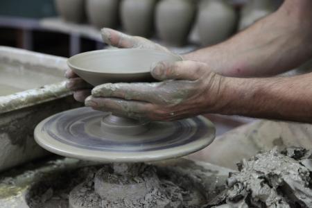 Поттер формировании чашу на гончарном круге. Руки Поттера, работающие на глиняной миски. Смазывание.
