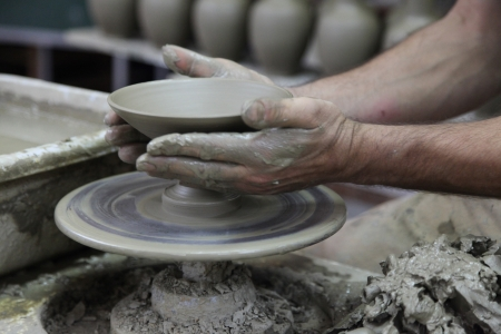 Potter shaping a bowl on a pottery wheel. Potter's hands working on clay bowl. Motion blur.