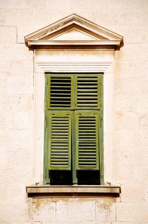 Vertical image of closed window with green shutters in old traditional  italian house  photo