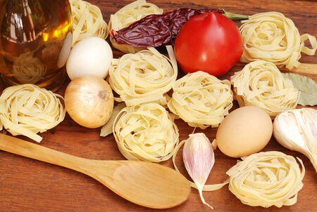 tagliatelle pasta, eggs,onion and tomato on wooden board photo