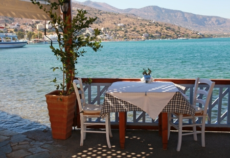 Beautiful traditional greek outdoor restaurant on terrace overlooking Mediterranean sea (Crete, Greece ). Stock Photo