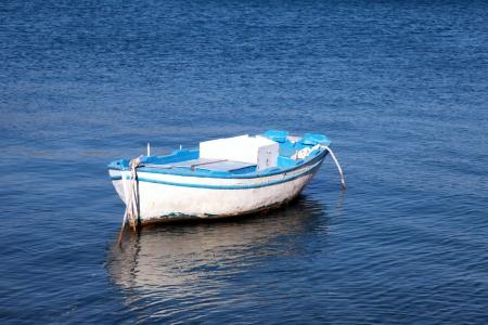 地中海の sea(Greece) での青と白の古い木製ボート