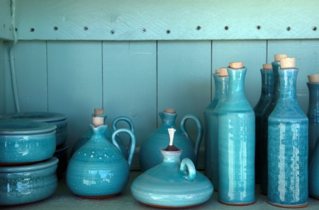 ceramic: turquoise glazed ceramic pitchers in green shelf , Crete , Greece