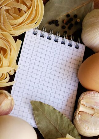Blank cookbook or shopping list with ingredients for pasta tagliatelle. selective focus photo