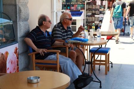 Агиос Николаос, Греция - 18 июля: Две старшие мужчины, сидя в открытом кафе на набережной улице Агиос Николаос (Крит, Греция) на 18 июля 2012 года. Местные мужчины традиционно побеседовать в кафе на открытом воздухе. Редакционное