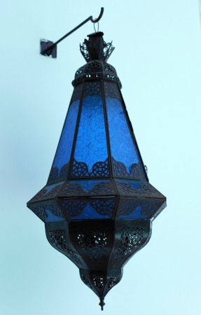Ornate traditional blue moroccan lamp hanging from a stucco wall Stock Photo