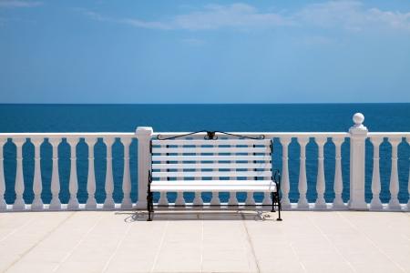 Летний вид с классической белой балюстрадой, скамейки и пустой террасе с видом на море Италии Фото со стока