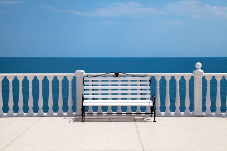Summer view with classic white balustrade, bench and empty terrace overlooking the sea  Italy  Stock Photo