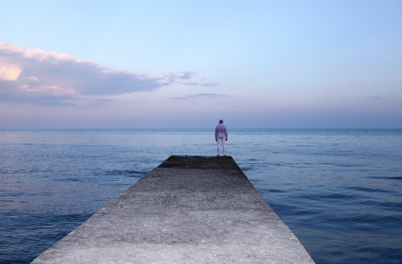 Lonely man watching the idillic sunset and blue sea on the pier
