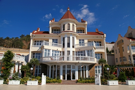 Elegant fasad of summer resort villa with classical white balconies on blue sky background