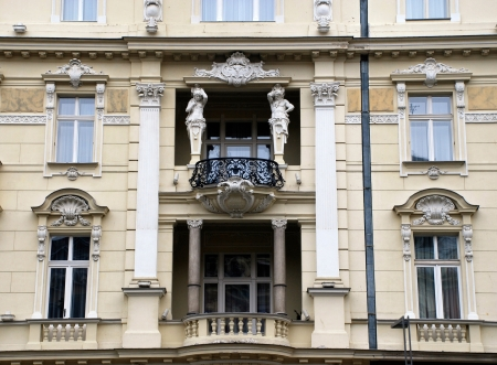 Ornate facade palace in baroque style with balkony and sculptures (Prague, Czech Republic).