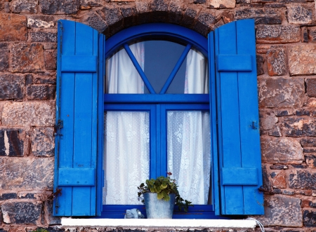Vintage blue window and shutter with flower pot set in old stone wall, Crete, Greece.  photo