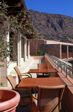 outdoor terrace with chairs and table and mountain view in a luxury resort(Crete, Greece) Vertical image