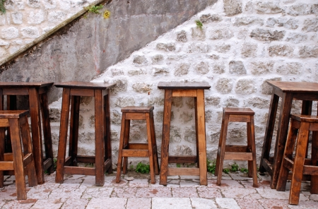 Outdoor cafe with wooden furniture and stone wall in small patio of old european town. Summer rain photo