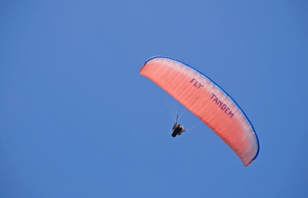 tandem paraglider, bright parachute in clear blue sky photo
