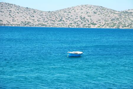 Blue and white wooden boat at a Mediterranean sea near Greek island coast(Greece) photo
