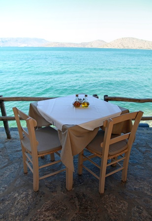 Table and rural chairs in greek outdoor restaurant with turquoise Mediterranean sea view(Crete, Greece). photo