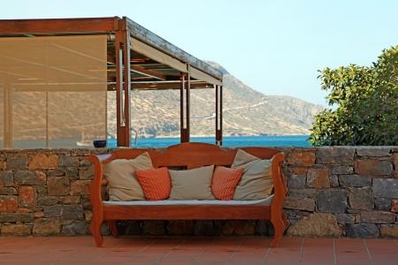 Красивая средиземноморская патио с видом на море, каменной стеной и наружной диван с подушками (Греция)
