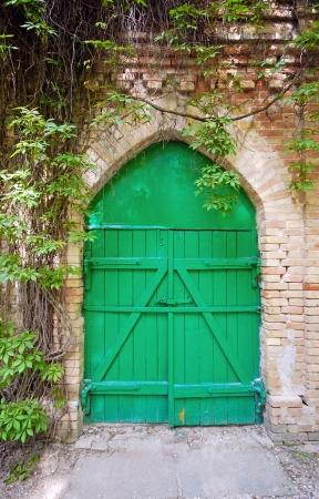 Старый зеленый деревянные ворота в сельской кирпичной стены