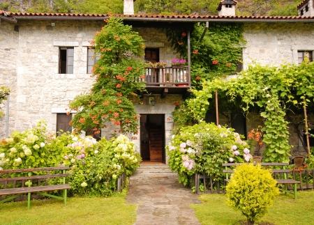 Идиллическая каменный сельский дом с красивым садом коттедж.
