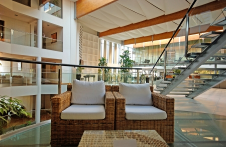 Modern hotel lobby with armchairs and glass steps in contemporary style