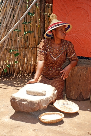 LESEDI CULTURAL VILLAGE,SOUTH AFRICA - JAN 1:Sotho woman in handmade dress  and conical hat cooking maize meal at tribal house on January 1,2008 at Lesedi Village, South Africa.Maize meal is basic African tribal ingredient.
