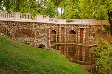 Pond with old beautiful stone grotto in summer park photo