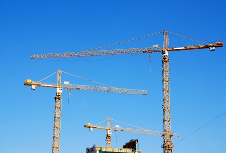 Tree cranes and building construction on blue sky background, horizontal image  photo