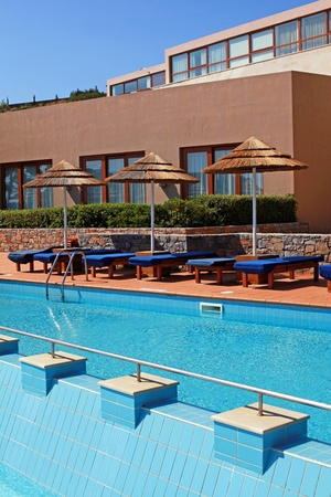 Beautiful outdoor poolside with pool bed and umbrella in summer luxury resort (Greece). Vertical image