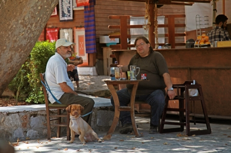 CRETE, GREECE - JULY 17: Two Greek men with dog sit at a rustic outdoor cafe set up at July 17, 2012 in the small greek village on Crete, Greece.  photo
