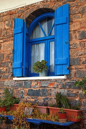 Vintage blue window with shutter and flower pot set in old stone wall  Crete, Greece   photo