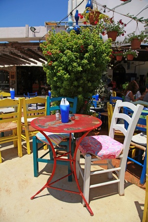 Beautiful outdoor restaurant with multicolored tables and chairs (Crete, Greece ). Vertical image photo