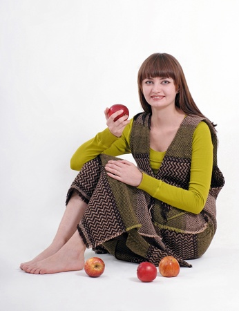 a girl is sitting on the floor and holding an apple (three more apples are lying nearby), white background photo