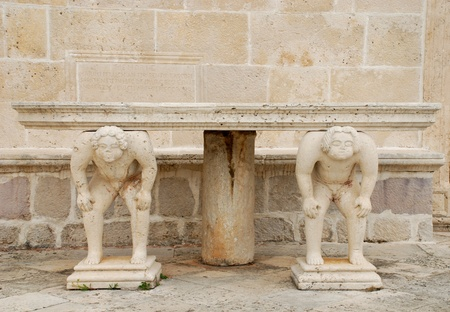 atlantes: Medieval mediterranean outdoor stone table with caryatids Editorial