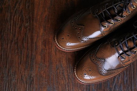 A pair of luxury brown shoes close up on wood background. photo