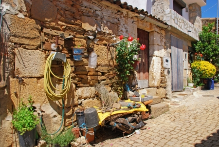 Vintage stone home with doorway, flowers and any trash in old Portugal village. photo