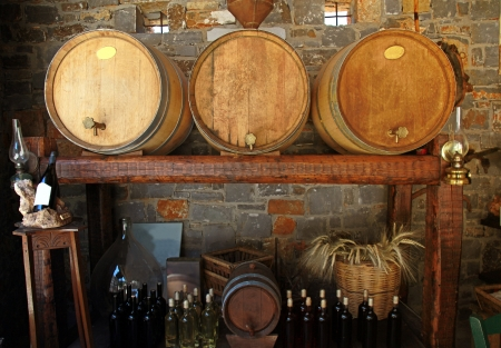 Wine barrels and bottles in the old cellar of a winery  photo
