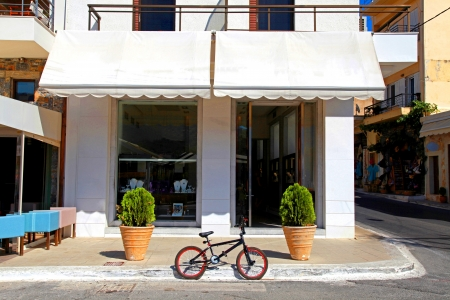 A bicycle parked on a street in front of house at old european town Crete, Greece   Banque d'images