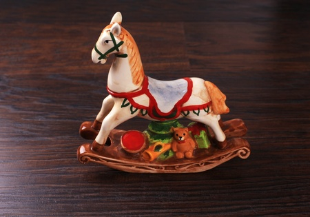 Vintage ceramic toy horse (christmas decoration also) on wood background. photo