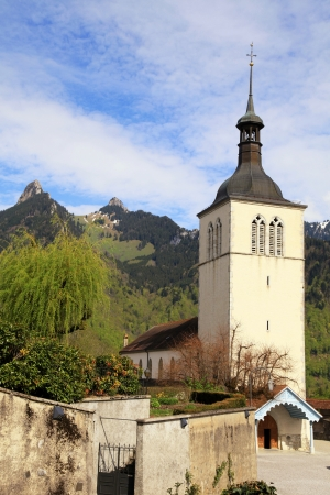 Church of Gruyeres and mountains in Swiss Alpes, Switzerland photo