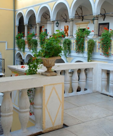 The interior of old hunting castle with white balustrade and flowers , Austria