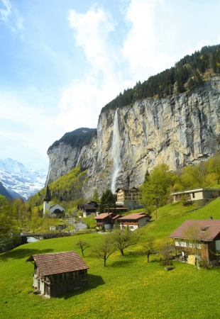 gstaad: Beautiful traditional mountain village with church and waterfall in the Alps, Switzerland . Vertical image