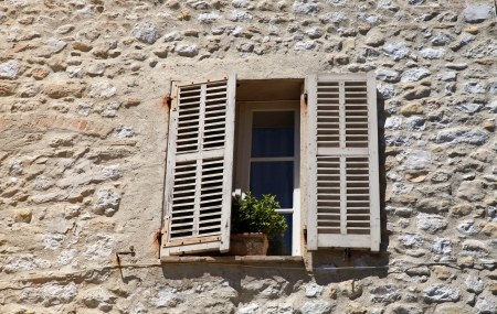 french rustic window with old wood shutters in stone rural house, Provence, France. photo