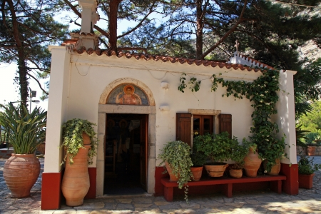 Beautiful small greek chapel with patio and flower pots in old mountain orthodox monastery Crete, Greece  photo